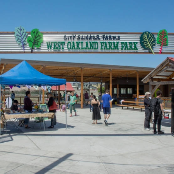 Large overhead sign for West Oakland Farm Park at park entrance, people strolling and shopping at market stalls
